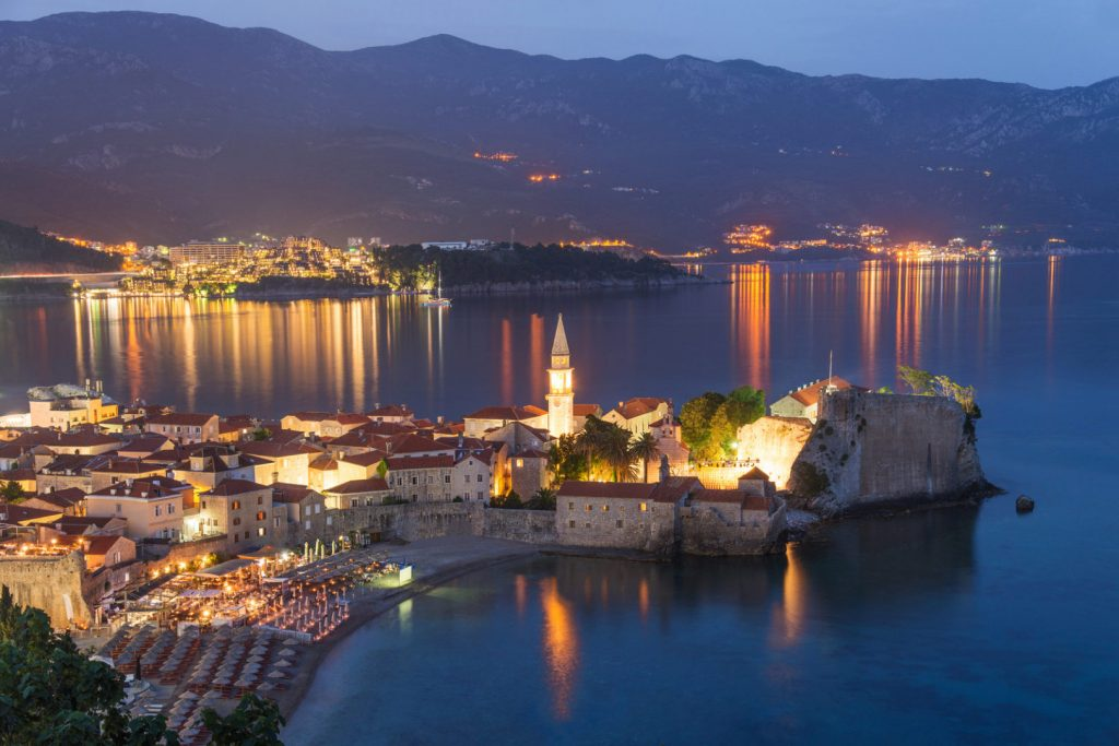 Budva old medieval walled city lights at night. Center of Montenegrin tourism, medieval walled city at Adriatic sea coastline. Montenegro. Europe.